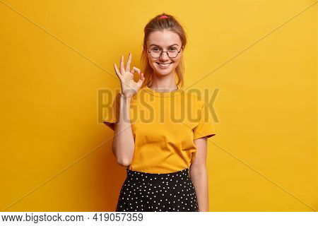 Pleased Young European Woman Makes Okay Gesture Shows Excellent Job Says Alright Satisfied With Good