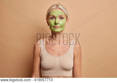 Half Length Shot Of Blonde European Woman Applies Nourishing Green Face Mask Uses Cosmetic Products