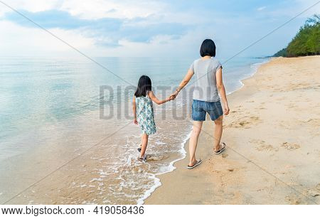 Back View Of Asian Mother And Little Daughter Are Walking Forward Along The Beach, Perspective View,