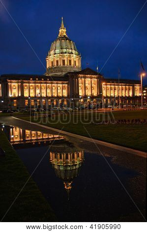 San Francisco City Hall at night after a rain reflected in a puddle