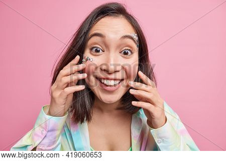 Portrait Of Cheeful Asian Woman With Toothy Smile Enjoys Hearing Positive News Touches Fresh Skin Ha