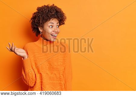 Horizontal Shot Of Happy Excited Woman Raises Palm Notices Something Unexpected And Surprising Smile