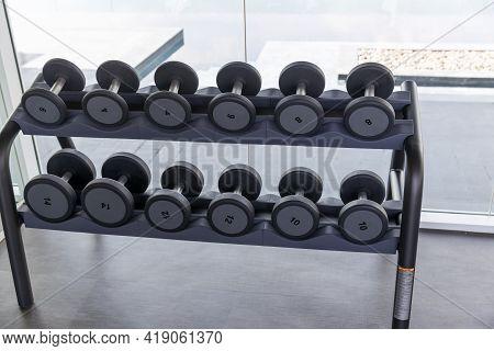 Dumbbell Set. Many Metal Dumbbells On Rack In Sport Fitness Center. Weight Training Equipment Concep