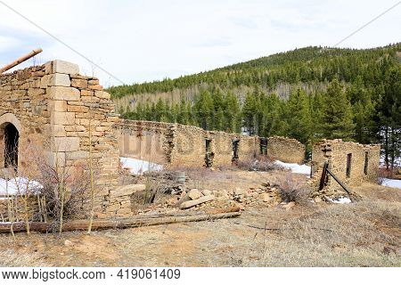 Abandoned And Collapsed Buildings On An Alpine Field Surrounded By A Temperate Pine And Aspen Forest