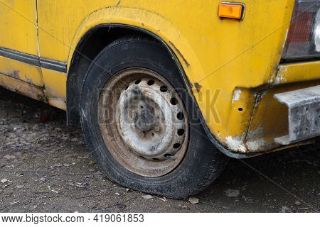 Abandoned, Old Car On The Street. Deflated Wheels., Close-up. Rust And Holes In The Body. Side View