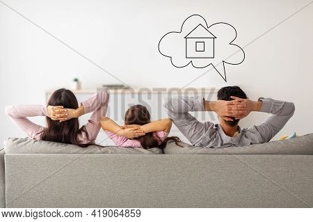 Back View Of Young Family Of Three Resting On Sofa And Man Daydreaming About Their New House