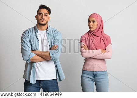 Relationship And Misunderstanding. Portrait Of Unhappy Muslim Spouses Standing Offended After Quarre