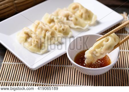 Steamed Wonton Dumpling Stuffed With Minced Pork And Shrimp On Plate Eating With Sesame Oil Sauce By