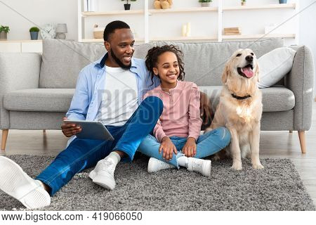 Black Family Spending Time Together With Dog At Home