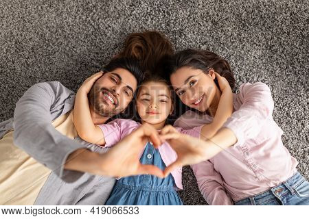 Happy Loving Family. Arab Parents And Liitle Daughter Lying On Floor Carpet And Holding Hands In Hea