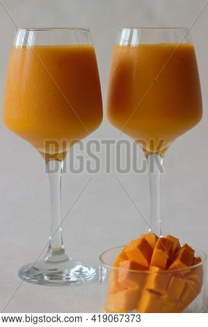 Two Glasses Of Mango Juice With Nicely Sliced Mango Kept Beside. Shot On White Background