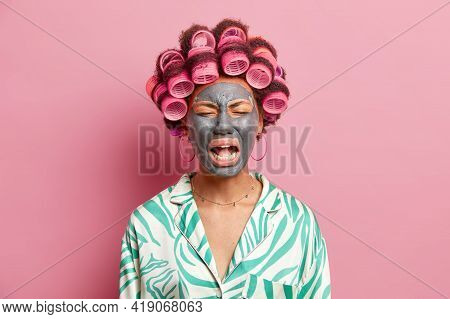 Depressed Sad Woman Cries Loudly Has Mournful Expression Applies Beauty Mask On Face Hair Rollers Pr