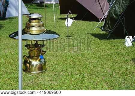 Close Up Image Of Vintage Hanging Brass Camping Lantern With Field Tents Group On Green Lawn In Camp