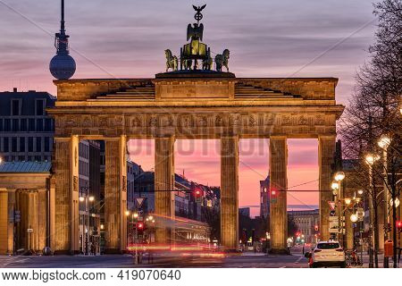 The Famous Brandenburg Gate In Berlin With The Television Tower Before Sunrise