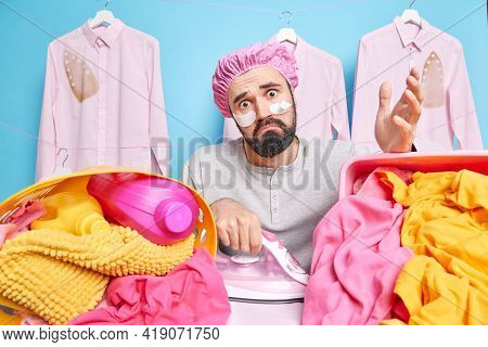Puzzled Surprised Hesitant Bearded Man Looks Clueless At Camera Uses Electric Iron For Ironing Cloth