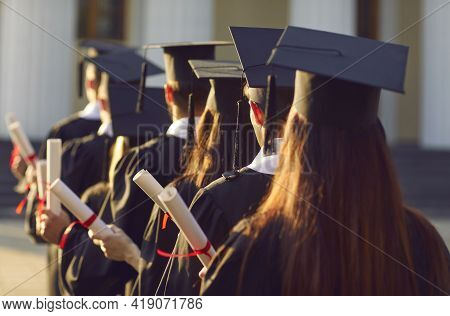 Group Graduate.university Graduates Line Up Hold Degree Award In Graduation Ceremony Rear View