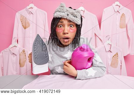 Stunned Afro American Woman Wears Sleepmask And Pajama Holds Bottle Of Detergent And Electric Iron D