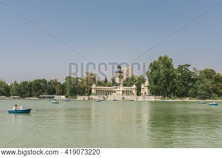 Madrid, Spain - August 8, 2018 - View Of Retiro Park And Floating People On Boats And Statue Of Alfo