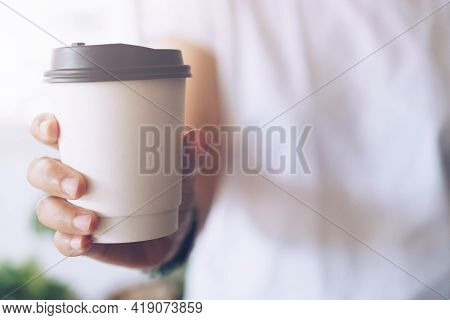 Hand Hold A Cup Of Coffee With Sunlight Flare Beautiful Copy Space Background. Wake Up Caffeine Inta
