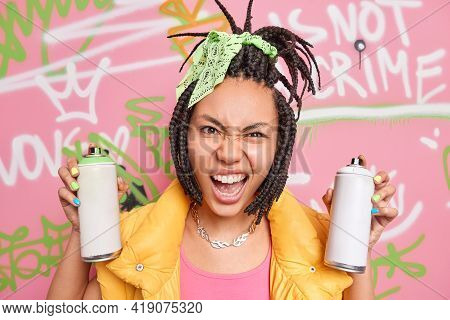 Modern Teenage Girl Has Dreadlocks Looks With Cheeky Face Expression At Camera Holds Two Aerosol Bot