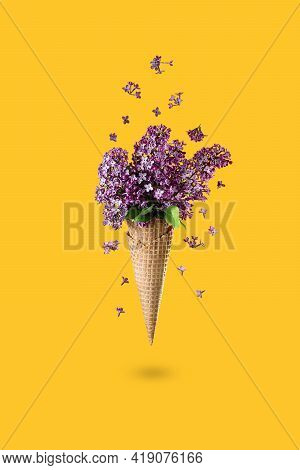 Ice Cream Of Lilac Flowers In Waffle Cone On Yellow Background From Above, Beautiful Floral Arrangem