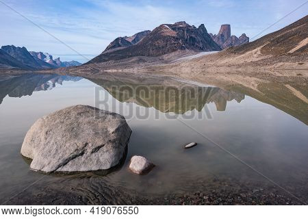 Granite Tower Of Mt.asgard And Surrounding Peaks Reflect In Waters Of Glacier Lake In Remote Arctic