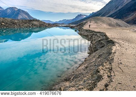 Hiker Walking By A Lake Through Remote Arctic Valley On A Partly Cloudy Summer Day. Dramatic Arctic