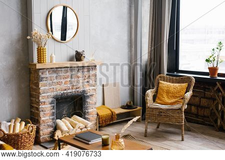 Cozy Interior Of The Living Room Rattan Chair And Fireplace. Rustic Design Of The House For A Warm I