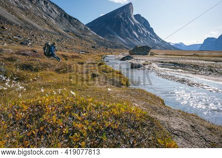 Hiker With Huge Backpack Rests By The River In Remote Arctic Landscape On A Sunny Summer Day. Passin