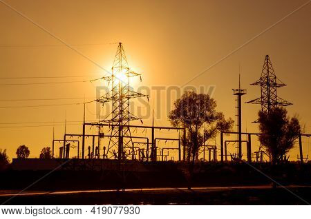 Power Substation And Power Lines On The Background Of The Sunset. Silhouette. Bright Colors. Concept
