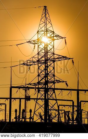 The Silhouette Of A Power Line Against The Background Of A Bright Yellow Sunset. Electrical Substati