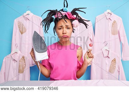 Unhappy Teenage Girl Doesnt Want To Do Ironing Has Funny Hairstyle Holds Lollipop And Electric Iron