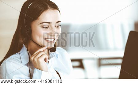 Brunette Female Customer Service Representative In A Headset Is Consulting Clients Online. Call Cent