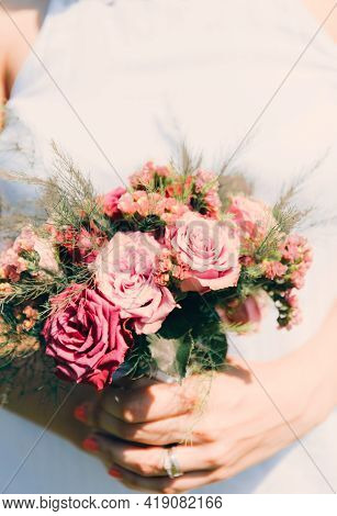 The Bride Holds A Wedding Bouquet From Roses In Her Hands, Wedding Day Flowers. Beautiful Bohemian W
