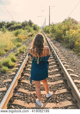 Beautiful And Attractive Woman In A Blue Dress Walking On The Railroad. Backview Image.