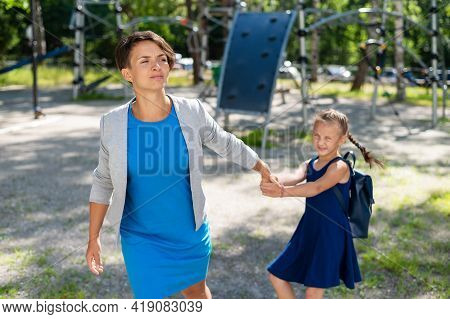 The Naughty Girl Pulls Her Mother By The Hand, Wanting To Stay On The Playground. The Capricious Dau