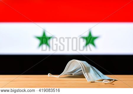 A Medical Mask Lies On The Table Against The Background Of The Flag Of Syria. The Concept Of A Manda