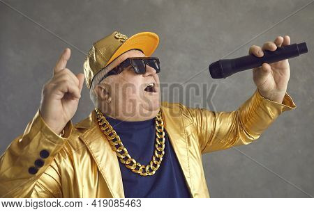 Studio Portrait Of Happy Chubby Senior Man With Microphone Rapping And Having Fun