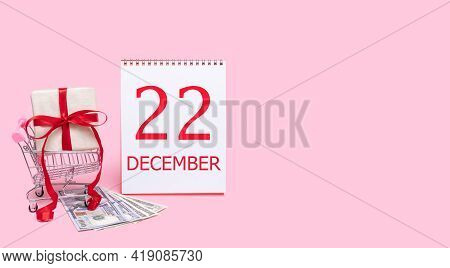 22nd Day Of December. A Gift Box In A Shopping Trolley, Dollars And A Calendar With The Date Of 22 D
