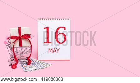 16th Day Of May. A Gift Box In A Shopping Trolley, Dollars And A Calendar With The Date Of 16 May On