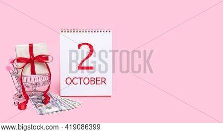 2nd Day Of October. A Gift Box In A Shopping Trolley, Dollars And A Calendar With The Date Of 2 Octo