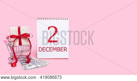 2nd Day Of December. A Gift Box In A Shopping Trolley, Dollars And A Calendar With The Date Of 2 Dec