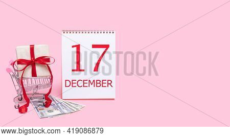 17th Day Of December. A Gift Box In A Shopping Trolley, Dollars And A Calendar With The Date Of 17 D