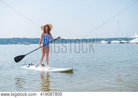 A Red-haired Woman In A Striped Swimsuit And A Straw Hat Floats On A Paddle Board In The Yacht Club