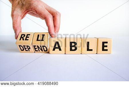 Dependable Or Reliable Symbol. Businessman Turns Wooden Cubes And Changes The Word Dependable To Rel