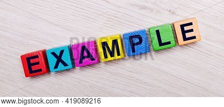 On A Light Wooden Background On Multi-colored Bright Wooden Cubes The Word Example