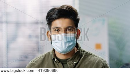 Close Up Portrait Of Young Cheerful Hindu Male Employee In Medical Mask Standing At Office, Looking