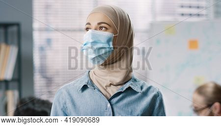 Close Up Portrait Of Young Arabic Beautiful Female Employee In Medical Mask Standing At Office At Wo