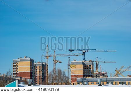 Construction Tower Cranes Build Monolithic Frame Houses And Brick Houses Against The Sky In The City