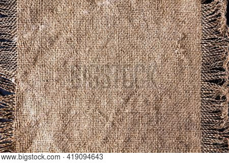 Closeup of rough canvas sackcloth with fringe.